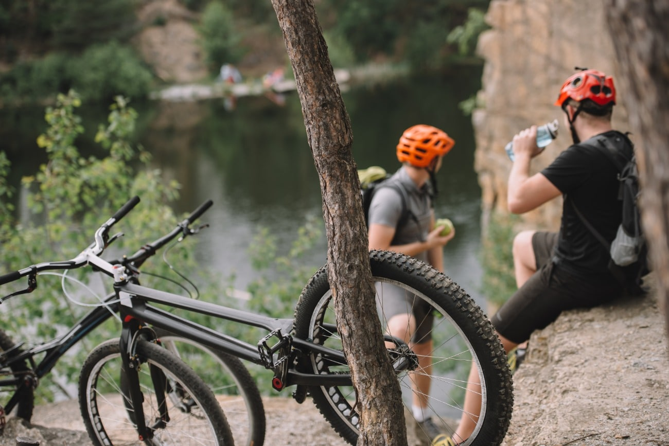 Two cyclists sitting on tree with bikes in foreground