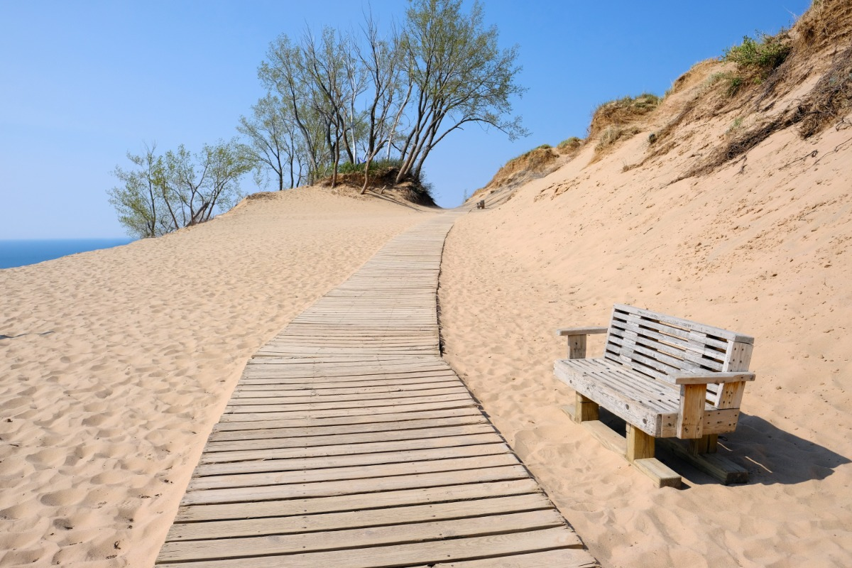 Wooden Bench next to wooden path with golden brown sand and blue skies