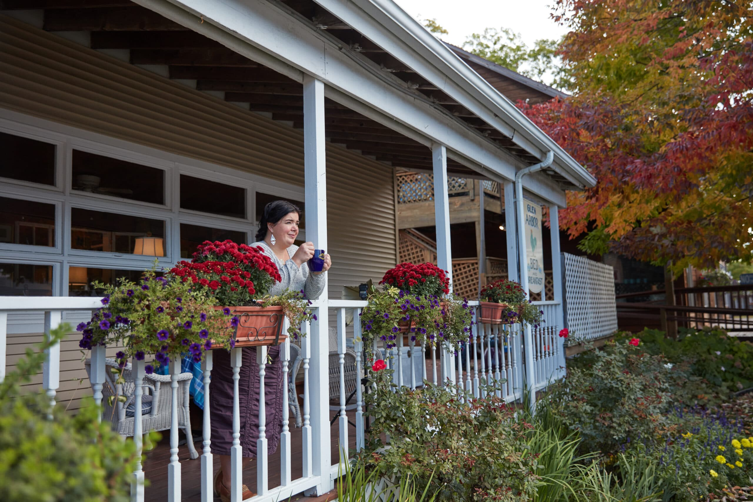 GABB, Laura on porch with coffee. Fall flowers in planters. Harrison 2020