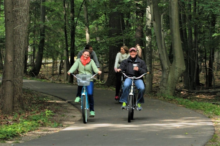 2 couples on bikes on paved trail through the woods