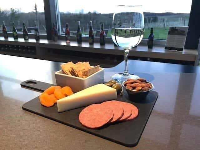 charcuterie board with glass of wine behind it all on brown countertop