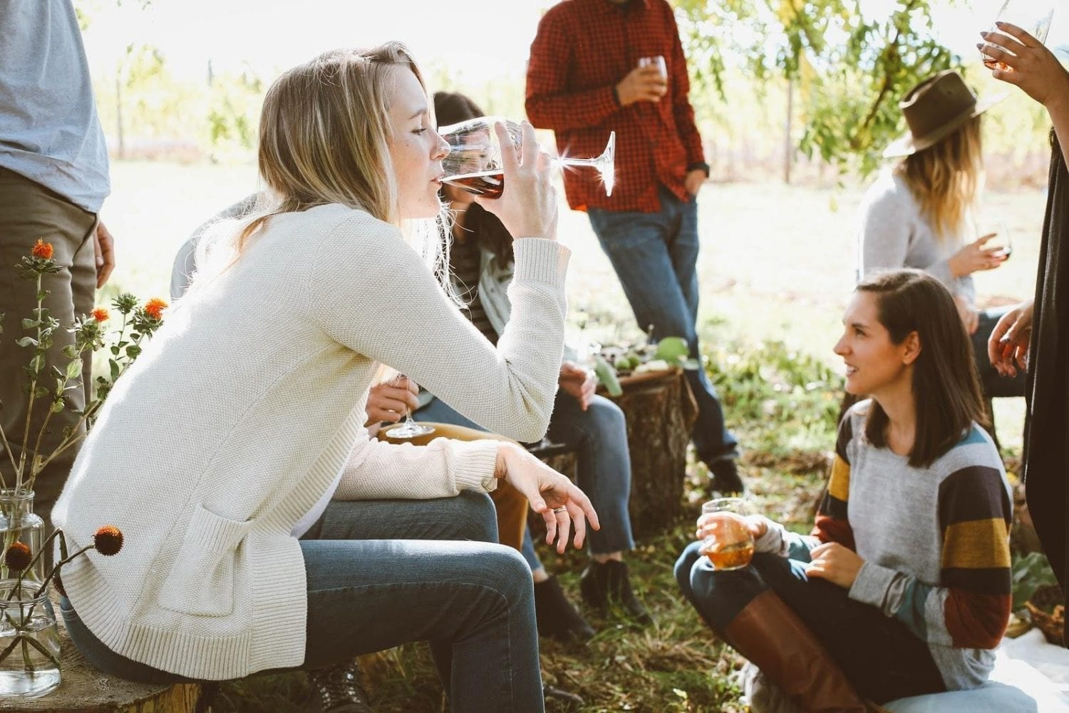 woman drinking red wine surrounded by other people outside drinking